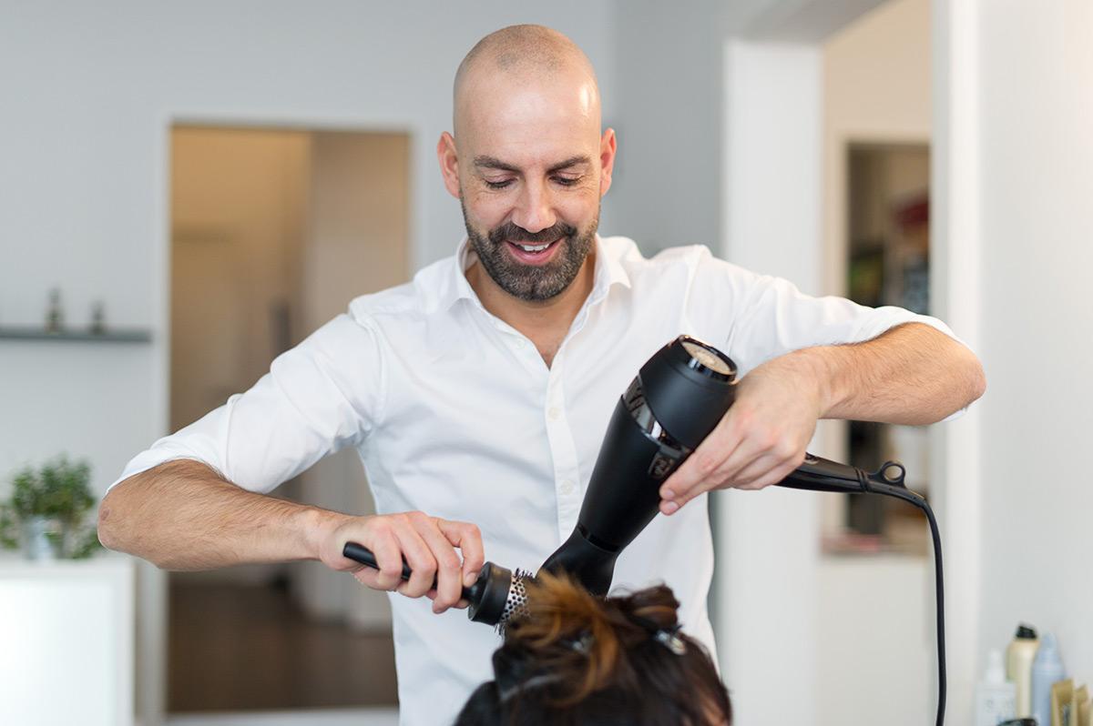 Friseur Arno Mitsch föhnt Kundin